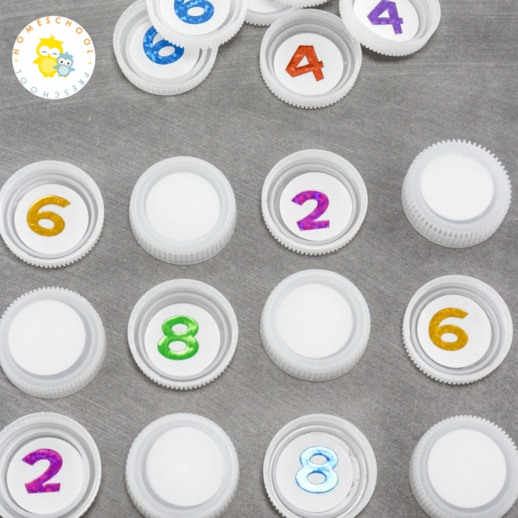 Come discover how to set up a low prep math game for preschoolers. All you need is some number stickers and some plastic bottle caps.