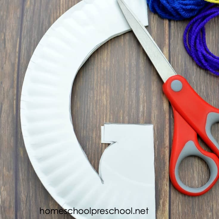 1. Fold the paper plate in half.  2. Most paper plates have a ridged boarder, trace this to form the inside circle. The pot of gold is simply a circle with a long skinny triangle on top. Any shaped pot will do, just make sure the top rim is large enough to create 6 hole punches.  3. Cut out the shape with scissors.  4. Hole punch 6 holes along the top of the pot of gold, one for each color of the rainbow.  5. Hole punch along the inside circle of the plate.  6. Color the pot of gold black, the bottom green for grass.  7. Start with the red yarn on the first pot of gold hole punch, thread through and tie to secure. Then thread through the boarder hole and back at the pot. Sporadically add a yellow pony bead to the yarn before threading it back through the next hole to fill the pot with gold (beads).  8. Follow this technique with all the colors of the rainbow, each color will have it's own hole at the top of the pot of gold. Secure each end on the back with a knot.  9. Your lucky rainbow pot of gold is complete